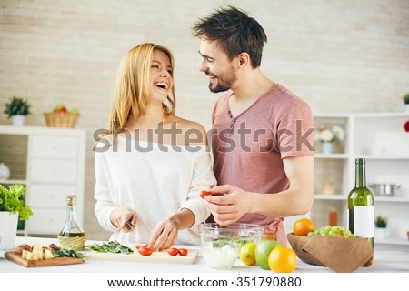 Young woman cutting tomatoes and looking at her husband - stock photo