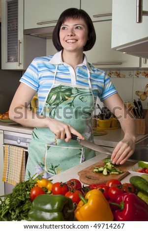 Young woman cutting vegetables in a kitchen.  Pretty girl in is cooking in the kitchen. home life: woman preparing something to eat. Smiling female standing and cutting cucumber in the kitchen.