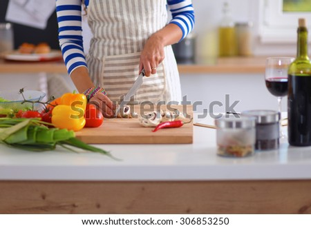 Young woman cutting vegetables in kitchen, standing near desk - stock photo