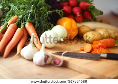 Young woman cutting vegetables in the kitchen - stock photo