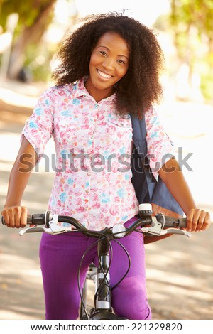 Young Woman Cycling Along Street To Work - stock photo