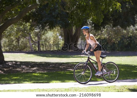 Young woman cycling in park, side view - stock photo