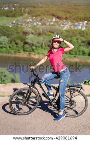 Young woman cycling on a clear blue day, with sunglasses and helmet.