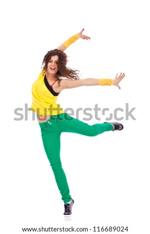 young woman dancer in a ballet pose with her leg and her arms extended to her side and smiling - stock photo