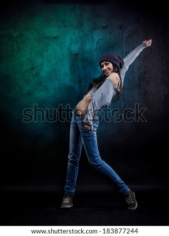 Young woman dancer on grungy wall background