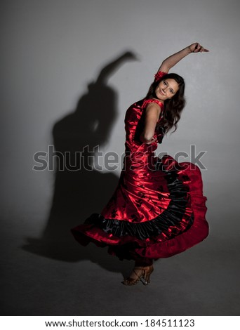 Young woman dancing flamenco, studio shot, gray background