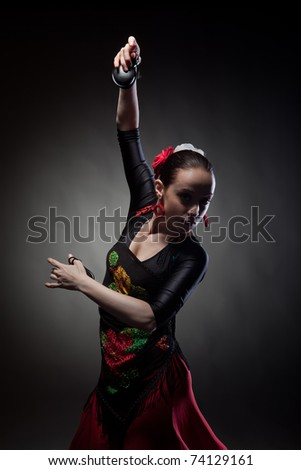 young woman dancing flamenco with castanets on black - stock photo