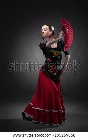 young woman dancing flamenco with fan on black - stock photo