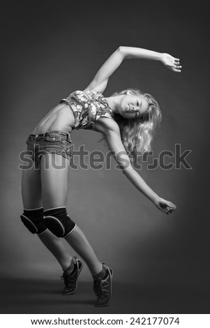 young woman dancing modern dance on dark background