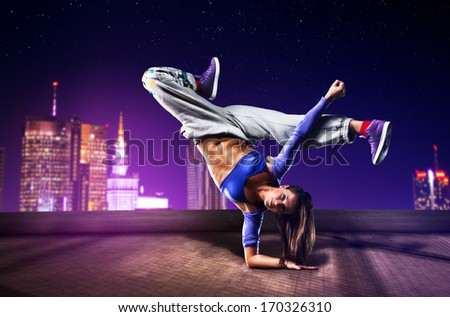 Young woman dancing on city background. - stock photo