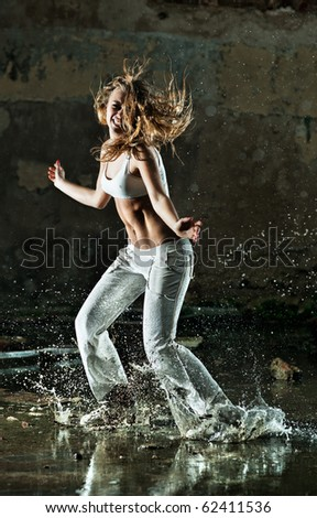 Young woman dancing on street with water.