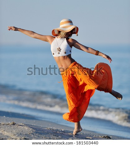 young woman dancing on the beach in summer - stock photo