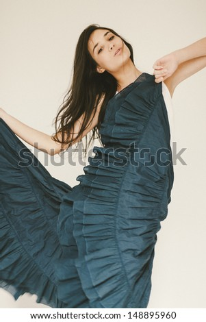 Young woman dancing. Shallow depth of field. Blur and strong grain added to create atmosphere. - stock photo