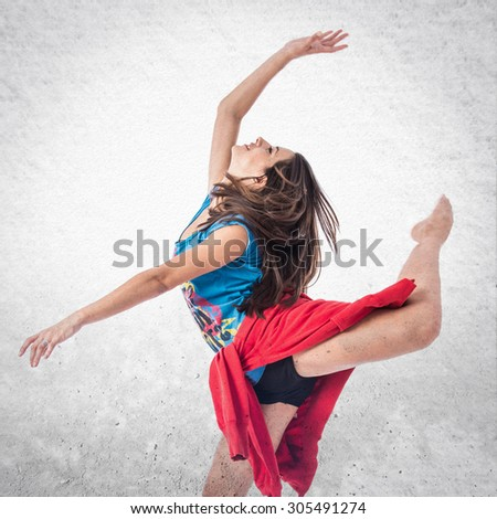 Young woman dancing street dance over textured background  - stock photo