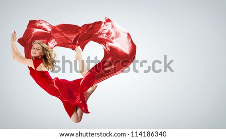 Young woman dancing with red fabric in studio and heart symbol