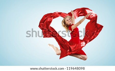 Young woman dancing with red fabric in studio and heart symbol - stock photo