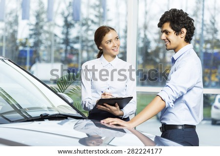 Young woman dealer in auto salon presenting car to customer