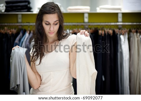 Young woman deciding which piece of clothing she likes more. In a clothing store.