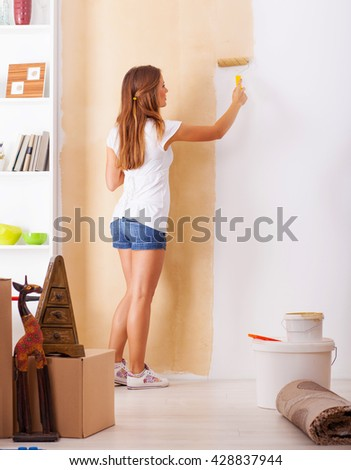 Young woman decorate her new apartment.She painted the wall. - stock photo