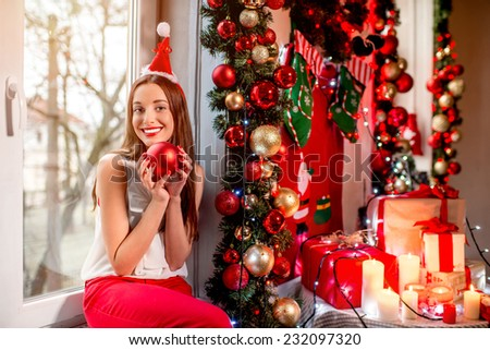 Young woman decorating Christmas tree with red balls at home - stock photo