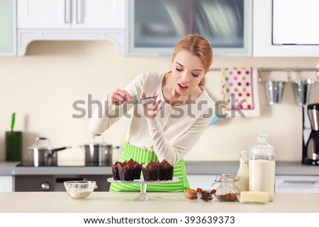 young woman decorating fresh baked cupcakes with a sugar powder