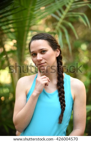 young woman deep in thought with finger on cheek - stock photo