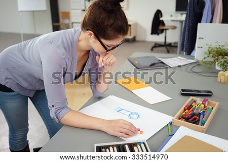 Young woman designing clothes in a studio leaning over a table sketching a fashion garment with colorful wax crayons - stock photo