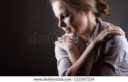 Young woman desperately crying on a dark background - stock photo