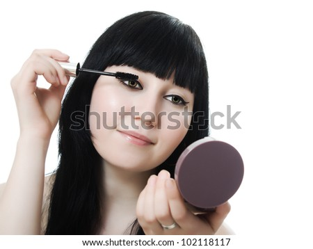 young woman directs a make-up eyelash on a white background.