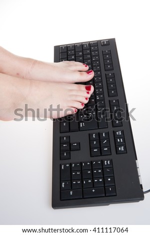 Young woman disabled using her foot on keyboard at her desk - stock photo