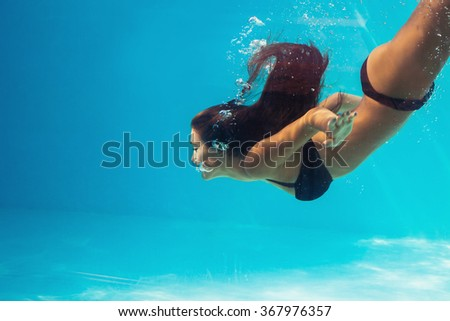 young woman dive in pool, profile, shot through the glass of the pool