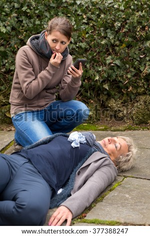 young woman do an emergency call, cause a senior adult is lying on the ground