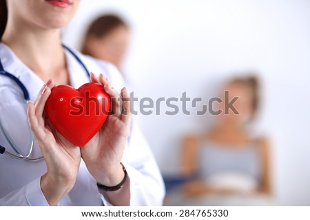 Young woman doctor holding a red heart, isolated on white  - stock photo