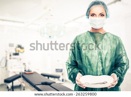Young woman doctor in cap and face mask holding medicine tray with surgery tools - stock photo