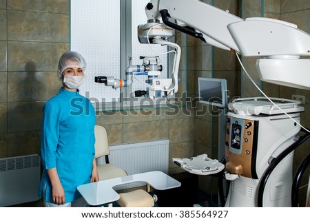 young woman doctor in operation room with surgical microscope. Ophthalmologist. medical, health, ophthalmology concept