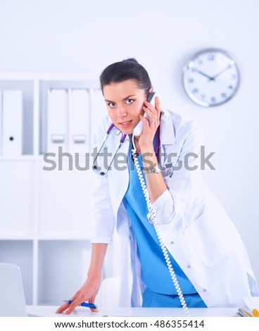 Young woman doctor in white coat at computer using phone