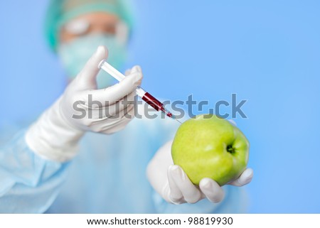 Young woman doctor injecting green apple with syringe on blue - stock photo