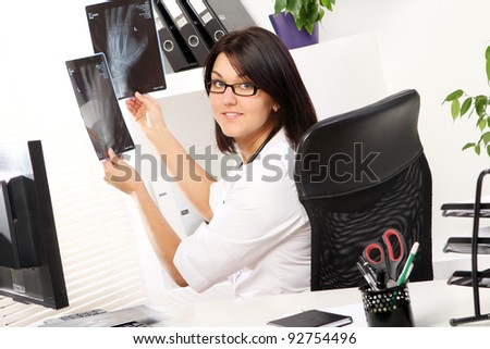 Young woman doctor is looking at xray of broken hand
