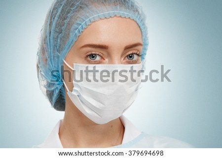 Young woman doctor or nurse in cap and face mask. - stock photo