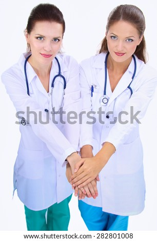 Young woman doctor stacking hands together over white background . - stock photo