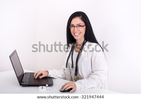 Young woman doctor working on laptop and looking at camera. Isolated on white background