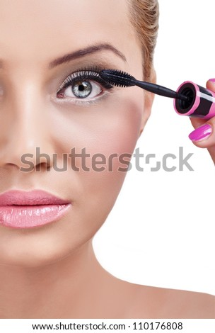 young woman does make-up and looking at camera as  mirror - stock photo