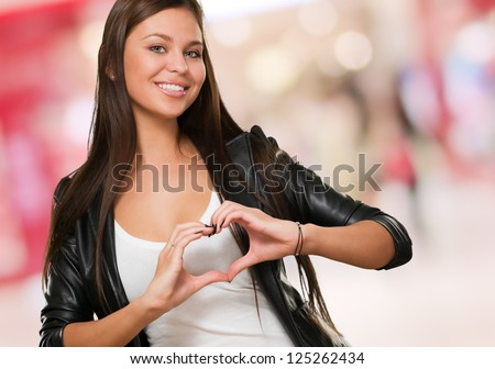 Young Woman doing a heart symbol, indoor - stock photo