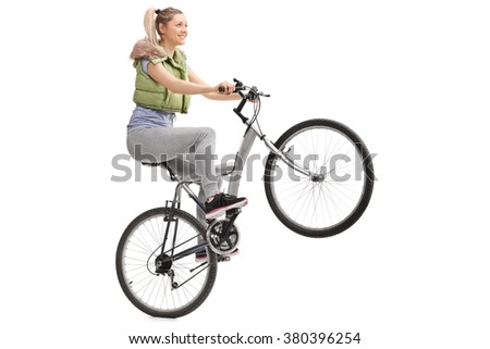 Young woman doing a wheelie on a bicycle isolated on white background