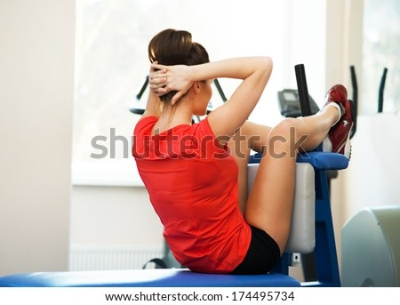 Young woman doing abdominal exercise in fitness club  - stock photo
