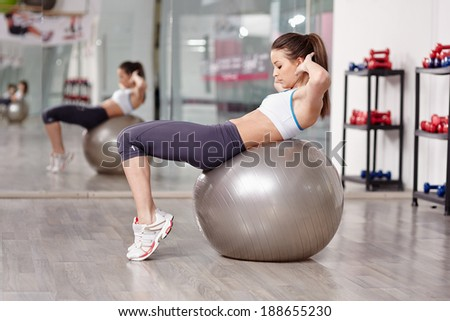 Young woman doing abs crunches with a ball in the gym - stock photo