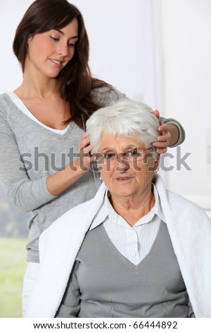 Young woman doing an haircut to old woman - stock photo