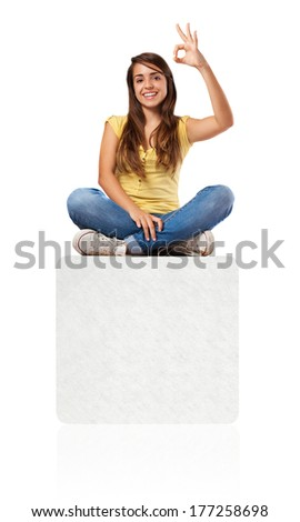 young woman doing approval sign sitting on a banner - stock photo