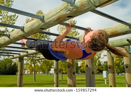Young woman doing Australian Pull-ups on a jungle gym. - stock photo