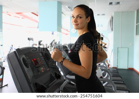 Young woman doing cardio exercises, running on treadmills in the gym - stock photo
